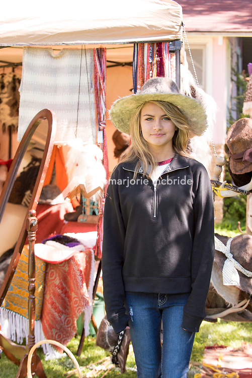Young lady trying on hand spun and woven hats at the Thousand Springs Art Festival at Ritter Island near Hagerman, Idaho. MR