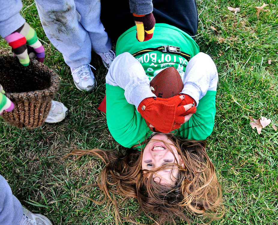 """(staff photo by Matt Roth)..Classmates' helping hands are offered to Seton Keough High School senior Julie Buonato, from Columbia, after completing a play during the school's Gatorbowl, Saturday November 22, 2008. The powder puff football tournament aims to raise money for juvenile diabetes, which Buonato has, which is why her powder puff name is """"The Cause.""""."""