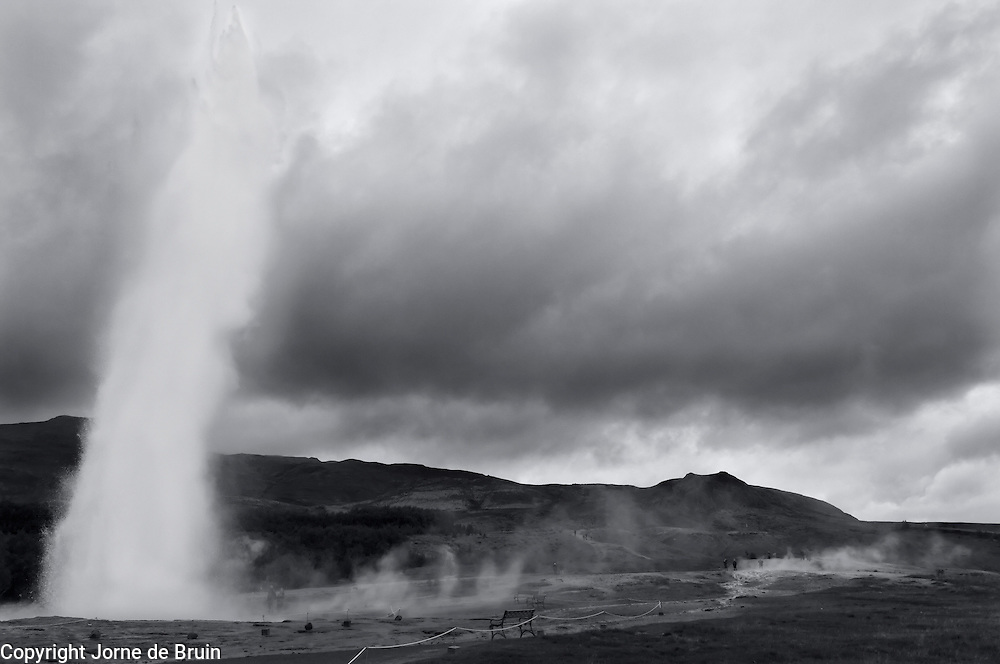 The Strokkur Geyser in Iceland erupts and spouts water and steam into the dark clouded sky in Iceland.