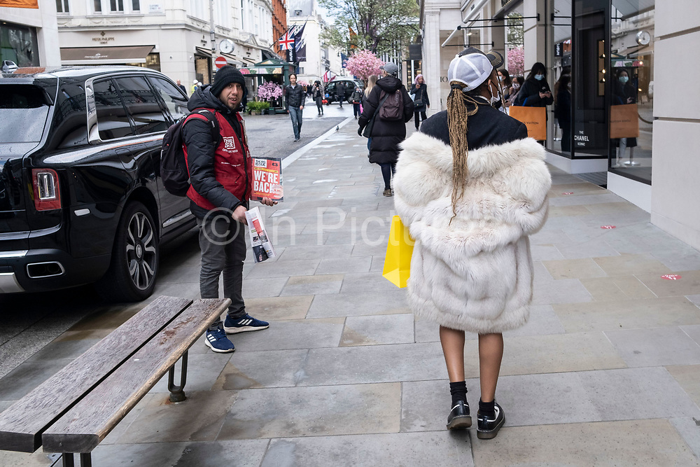 Woman wearing a fake fur coat passes a Big Issue seller at the exclusive shopping area on Bond Street as non-essential shops reopen and the national coronavirus lockdown three eases on 15th April 2021 in London, United Kingdom. Now that the roadmap for coming out of the national lockdown has been laid out, this is the first phase of the easing of restrictions, and large numbers of people are out in Londons retail district laden with shopping bags.