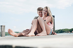Teenage couple sitting on a jetty at lake