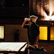 A spectator drinks a beer during a practice session for team Hostel X.