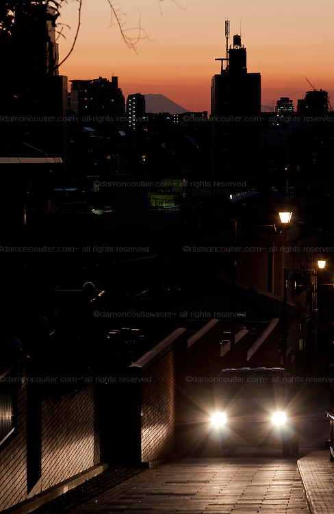 A van ascends the road during sunset over Fujimizaka (Mount Fuji viewing Hill) in Nishi Nippori, Tokyo, Japan. Friday January 11th 2013. This is the last street level place in central Tokyo to see Mount Fuji and is threaten with development that will block the view of this iconic peak.