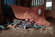 Carlos Guimaraes a Shipibo-Konibo elder lies inside the mosquito net with strong symptoms of Covid-19. He is cared for by his family, his daughter and wife as the Shipibo indigenous health protocol dictates to guard his health.