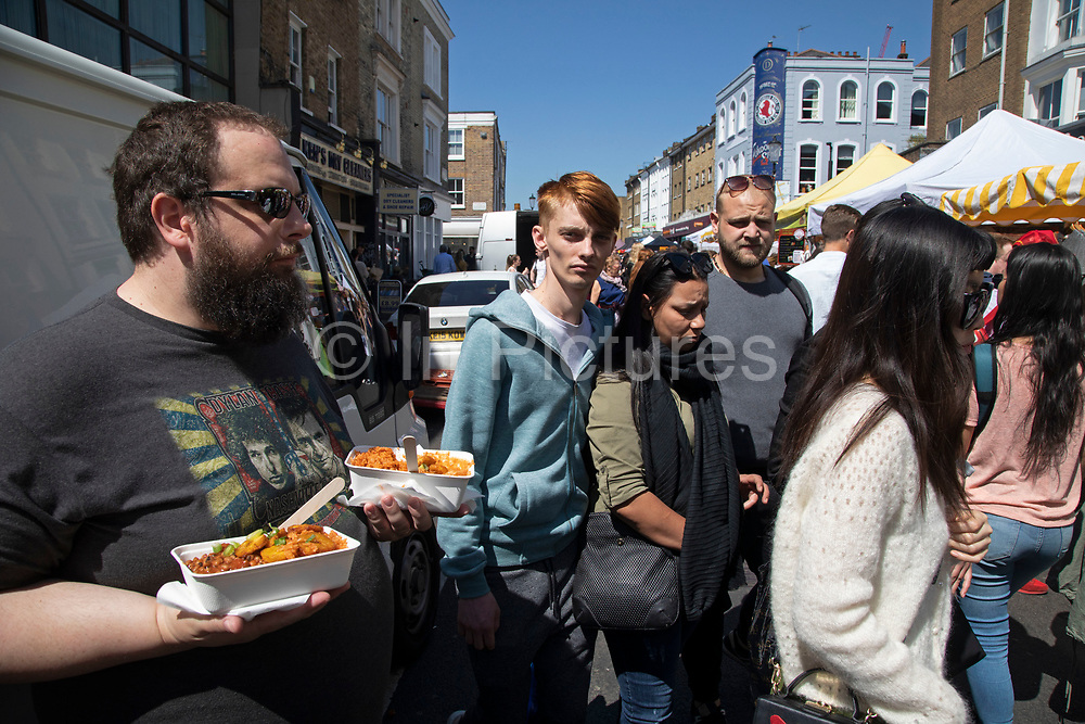 Portobello Road Market food in Notting Hill, West London, England, United Kingdom. People enjoying a sunny day out hanging out at the famous Sunday market, when the antique stalls line the street.  Portobello Market is the worlds largest antiques market with over 1,000 dealers selling every kind of antique and collectible. Visitors flock from all over the world to walk along one of Londons best loved streets.