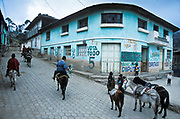 Native indian farmers riding on donkeys  through the town of Angamarca heading for the market, Ecuador.