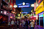 Busy streets with colourful lighting and lots of people very busy, near Beatlesplatz, Reeperbahn and St Pauli, Hamburg, Germany.