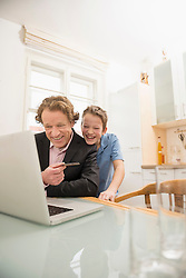 Father and son with laptop and credit card