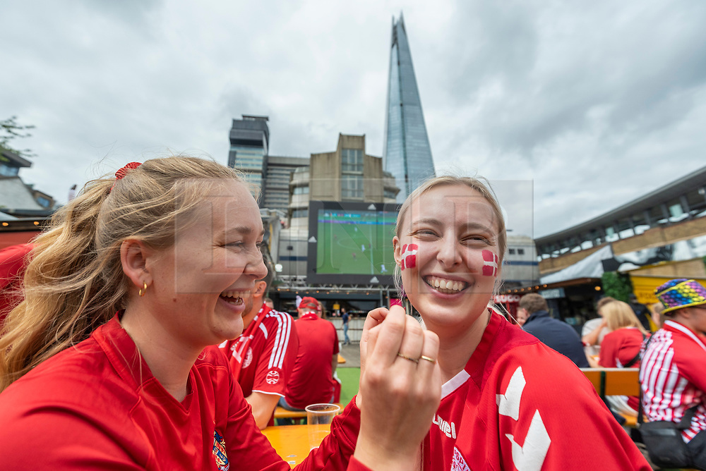 © Licensed to London News Pictures. 07/07/2021. LONDON, UK.  Denmark football fans apply facepaint in Vinegar Yard, Bermondsey, ahead of the Euro 2020 semi-final between England and Denmark at Wembley Stadium.  Photo credit: Stephen Chung/LNP