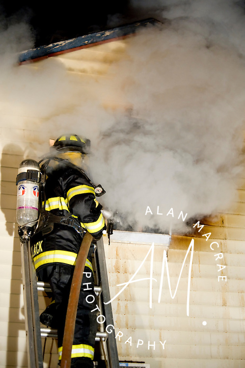 Laconia firefighter Deb Black pours water in on the fire as heavy smoke and steam pour out at a single alarm fire in Laconia early Tuesday morning.  The fire destroyed Gulbicki's Towing Service garage, a Weirs Beach landmark.  (Alan MacRae/for the Monitor)