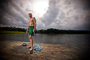 An elderly man stands on a pier in his swim trunks after taking a dip in the lake.