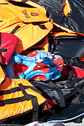 Greece. Lesvos. Petra. Discarded life jackets, including a child's Spiderman one, from newly arrived refugees.