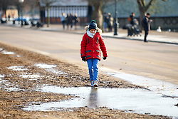 © Licensed to London News Pictures. 03/01/2017. London, UK. A child walks over frozen puddles in Hyde Park, London on a frosty morning as temperatures in the capital drop below zero celsius on Tuesday, 3 January 2017. Photo credit: Tolga Akmen/LNP