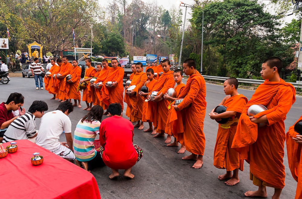 Young Buddhist monks receiving alms, near the Kruba Sriwichai Monument, Chiang Mai, Northern Thailand