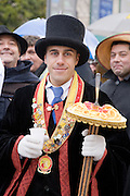 A character in Verona's carnival parade, holding a model plate of spaghetti or bigoli pasta with a fork.