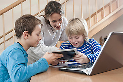 Two boys and female childcare assistant with laptop and tablet computer