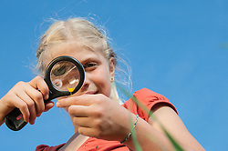 Girl (10-11) examining flower through magnifying glass, low angle view, close-up