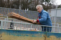 Man putting wood into the skip at the Tipsmart recycling centre at Calverton,