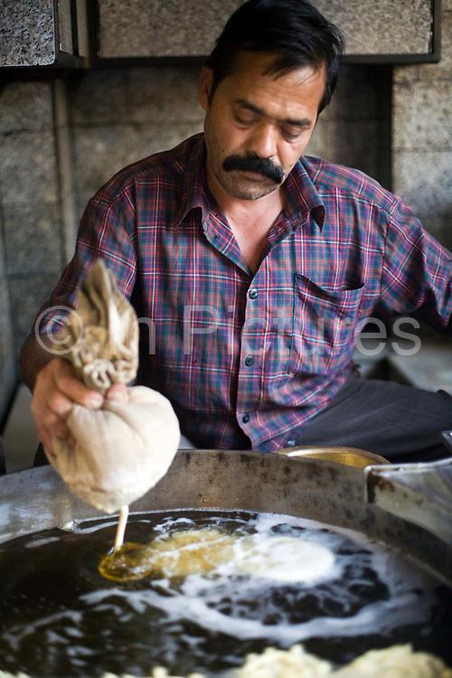 A man squeezes batter from a cloth to make jalebis at the Old and Famous Jalebi Wala (at the corner of Dariba Kalan and Chandni Chowk). Delhi, India