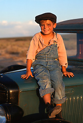Young boy with a black eye sitting on top of an old truck