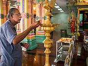 05 JUNE 2015 - KUALA LUMPUR, MALAYSIA:   A man lights incense in the main prayer hall in Sri Mahamariamman Temple, the oldest functioning and most important Hindu temple in Malaysia. The principal deity in the temple is Mariamman,  a deity that is popularly worshipped by overseas Indians, especially Tamils, because she is looked upon as their protector during the sojourn to foreign lands. Mariamman is a manifestation of the goddess Parvati, an incarnation embodying Mother Earth with all her terrifying force. She is associated with disease and fever and protects her devotees from unholy or demonic events.    PHOTO BY JACK KURTZ