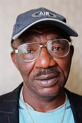 Portrait of man wearing baseball cap and glasses looking sad,