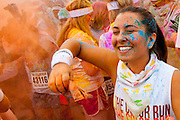 Participants in charity 10K road race celebrate their finish by throwing packets of colorful powered dye into the air.