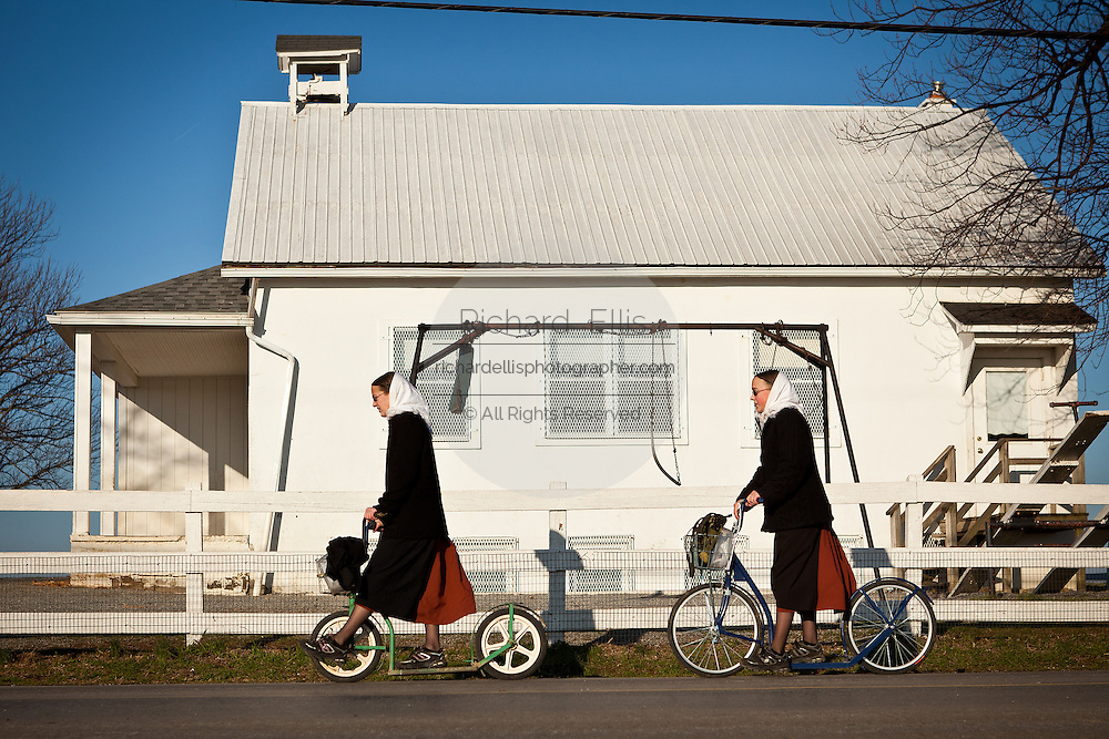 Amish girls ride a push scooter in Gordonville, PA.