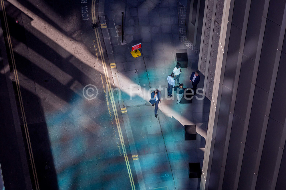 Looking down from an aerial view towards small business figures walking through blue reflected light in the City of London, the capitals ancient financial district, on 13th May, in London, England.