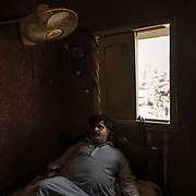 During a rolling black out, Seraj Udin,  hotel owner takes a break in his hotel, the Greenland Hotel.