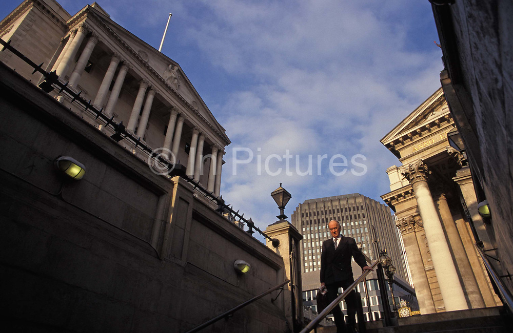 Beneath the columns of the Bank of England left and Cornhill Exchange right an older City gentleman descends the steps into Bank underground station, on 20th April 1994, in London, England.