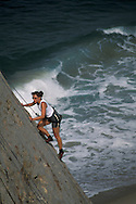 Female rock climber climb cliff over ocean water waves at Point Dume State Beach near Malibu, Los Angeles County, California