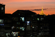 Old buildings and inner city with Shwedagon Pagoda rising above, before sunrise, Yangon