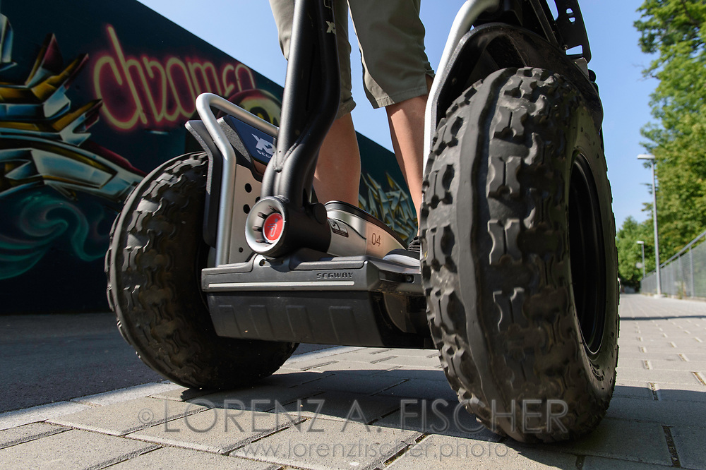 A group of young people is enjoying a ride with off road segways in the city of Frauenfeld along a wall with graffiti on a nice, sunny summer day in July, Thurgau, Switzerland