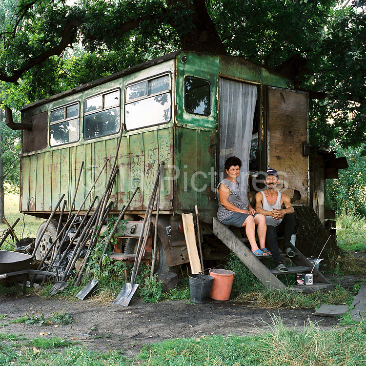 Charcoal burners sit outside their home where they stay during the summer to make charcoal, Viscri, Romania
