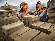 03 MARCH 2017 - BAGMATI, NEPAL: Workers load bricks into packs to carry them to a kiln at a brick factory in Bagmati, near Bhaktapur. There are almost 50 brick factories in the valley near Bagmati. The brick makers are very busy making bricks for the reconstruction of Kathmandu, Bhaktapur and other cities in the Kathmandu valley that were badly damaged by the 2015 Nepal Earthquake. The brick factories have been in the Bagmati area for centuries because the local clay is a popular raw material for the bricks. Most of the workers in the brick factories are migrant workers from southern Nepal.       PHOTO BY JACK KURTZ