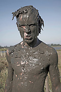 Young man face covered in mud angry face - model released