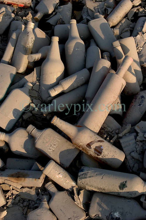 30 Sept, 2005.  New Orleans, Louisiana. Lower 9th ward. Hurricane Katrina aftermath. <br /> The remnants of the lives of ordinary folks, now covered in mud as the flood waters recede. The remnants of  a liquor store lies scattered in the dirt.<br /> Photo; ©Charlie Varley/varleypix.com