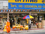 """12 NOVEMBER 2012 - BANGKOK, THAILAND:  A monk crosses Bamrung Muang Street in Bangkok. Thanon Bamrung Muang (Thanon is Thai for Road or Street) is Bangkok's """"Street of Many Buddhas."""" Like many ancient cities, Bangkok was once a city of artisan's neighborhoods and Bamrung Muang Road, near Bangkok's present day city hall, was once the street where all the country's Buddha statues were made. Now they made in factories on the edge of Bangkok, but Bamrung Muang Road is still where the statues are sold. Once an elephant trail, it was one of the first streets paved in Bangkok. It is the largest center of Buddhist supplies in Thailand. Not just statues but also monk's robes, candles, alms bowls, and pre-configured alms baskets are for sale along both sides of the street.    PHOTO BY JACK KURTZ"""