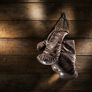 A pair of vintage boxing gloves hanging on an old wooden wall with atmospheric lighting.