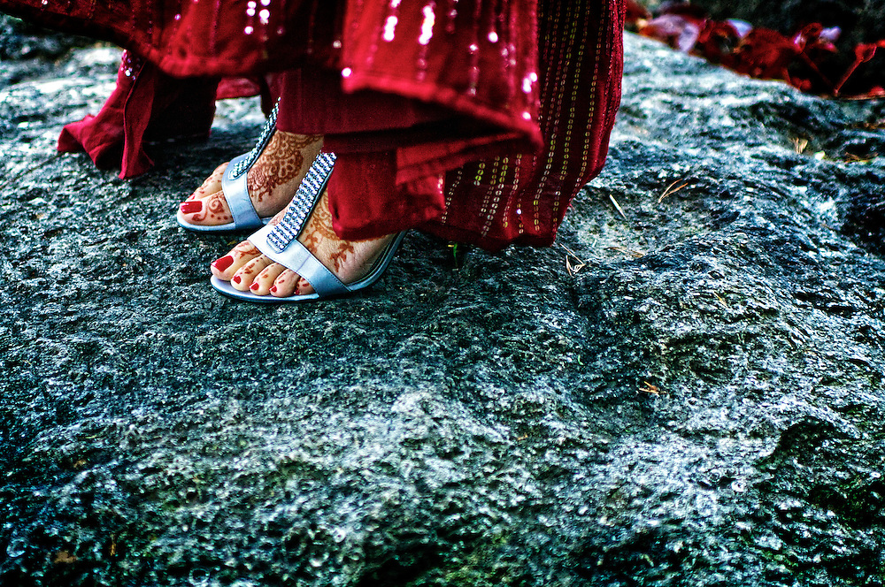 The bride's feet are adorned with traditional Henna for her traditional Hindu wedding ceremony.
