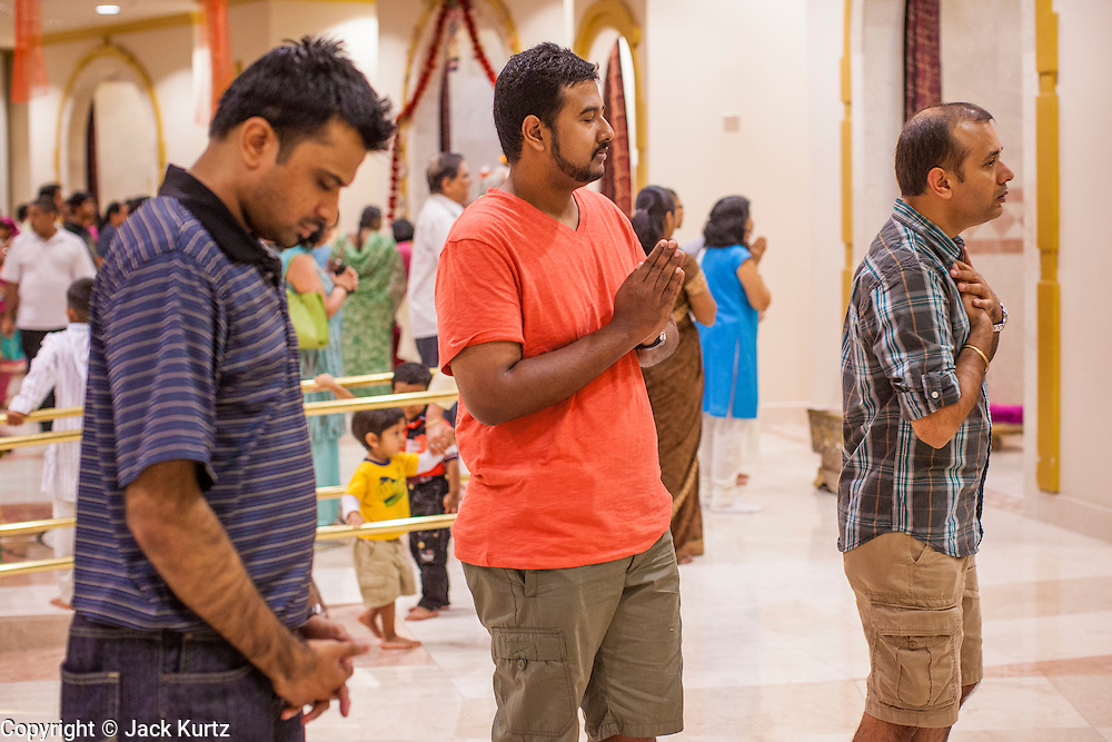 10 AUGUST 2012 - PHOENIX, AZ:   Men pray at the mandirs that house shrines in the temple during the celebration of Janmashtami at Ekta Mandir, a Hindu temple in central Phoenix. Janmashtami is the Hindu holy day that celebrates the birth of Lord Krishna. Hindu communities around the world celebrate the holy day. In Arizona, most of the Hindu temples in the Phoenix area have special celebrations of the day.    PHOTO BY JACK KURTZ