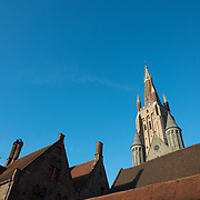 Roof tops of historic buildings in Bruges, Belgium, with the spire of the Church of Our Lady towering above.