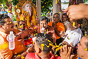 """15 SEPTEMBER 2013 - BANGKOK, THAILAND:  Hindus in Bangkok sing and pray and throw marigolds to the deities on the last day of Ganesha Chaturthi celebrations at Shiva Temple in Bangkok. Ganesha Chaturthi is the Hindu festival celebrated on the day of the re-birth of Lord Ganesha, the son of Shiva and Parvati. The festival, also known as Ganeshotsav (""""Festival of Ganesha"""") is observed in the Hindu calendar month of Bhaadrapada. The festival lasts for 10 days, ending on Anant Chaturdashi. Ganesha is a widely worshipped Hindu deity and is revered by many Thai Buddhists. Ganesha is widely revered as the remover of obstacles, the patron of arts and sciences and the deva of intellect and wisdom. The last day of the festival is marked by the immersion of the deity, which symbolizes the cycle of creation and dissolution in nature.  In Bangkok, the deity (statue) was submerged in the Chao Phraya River.        PHOTO BY JACK KURTZ"""