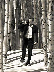 man in a suit and snowshoes walking through an Aspen Forest in New Mexico