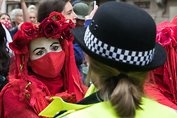 London, UK. 23rd August, 2021. Members of the Extinction Rebellion Red Rebel Brigade line up in front of Metropolitan Police officers during the first day of Impossible Rebellion protests in the Covent Garden area. Extinction Rebellion are calling on the UK government to cease all new fossil fuel investment with immediate effect. Credit: Mark Kerrison/Alamy Live News