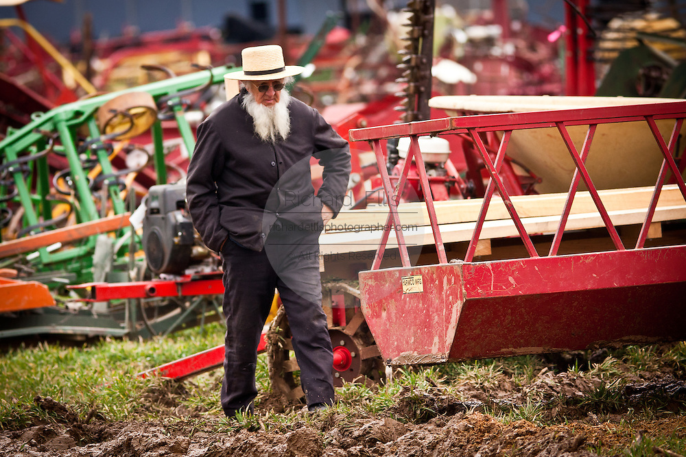 Elderly Amish man walks past farm equipment during the Annual Mud Sale to support the Fire Department  in Gordonville, PA.