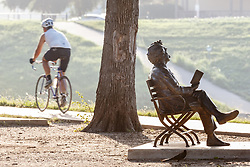 Cyclist on the Trinity Trails near the Trinity River passing sculpture of Mark Twain reading book, Fort Worth, Texas, USA.