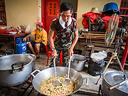 "09 AUGUST 2014 - BANGKOK, THAILAND:      A volunteer cooks chicken with basil for people waiting for free food at the Ruby Goddess Shrine in the Dusit section of Bangkok. The seventh month of the Chinese Lunar calendar is called ""Ghost Month"" during which ghosts and spirits, including those of the deceased ancestors, come out from the lower realm. It is common for Chinese people to make merit during the month by burning ""hell money"" and presenting food to the ghosts. At Chinese temples in Thailand, it is also customary to give food to the poorer people in the community.    PHOTO BY JACK KURTZ"