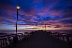 May 6, 2019 - Christchurch, New Zealand - Clouds above the beach and pier light up dramatically as the sun rises at New Brighton Beach in Christchurch, New Zealand on May 05, 2019. (Credit Image: © Sanka Vidanagama/NurPhoto via ZUMA Press)